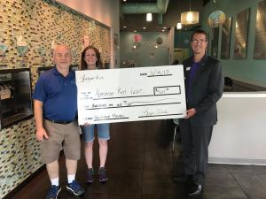 Three people holding a giant check.